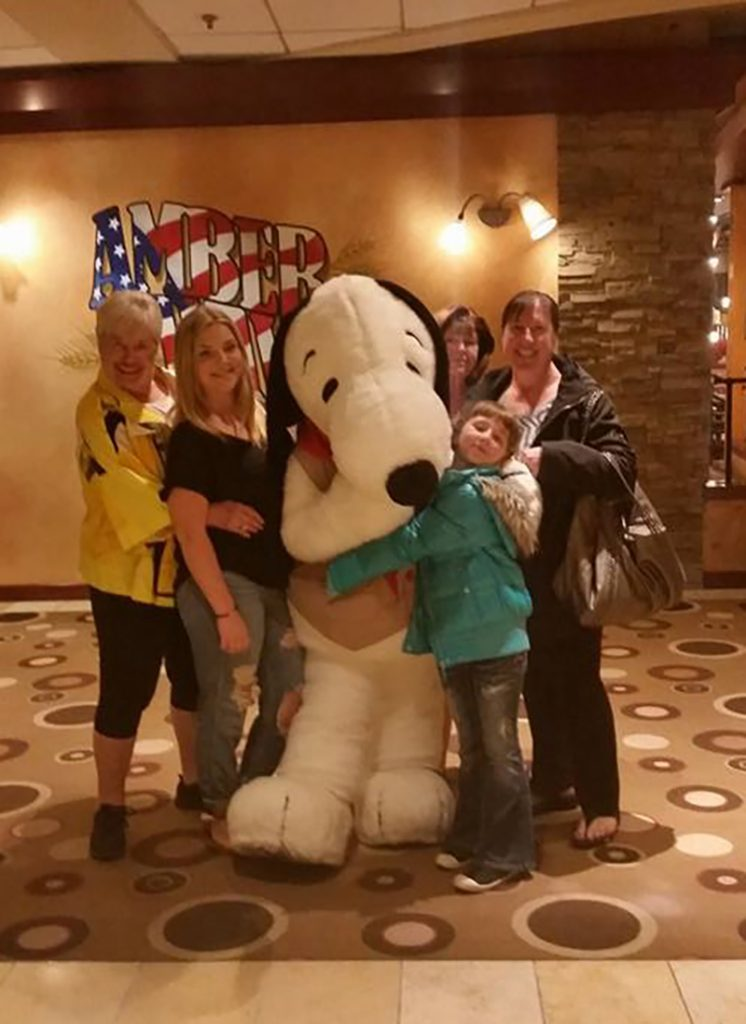 A whole family smiling and hugging a life size Snoopy
