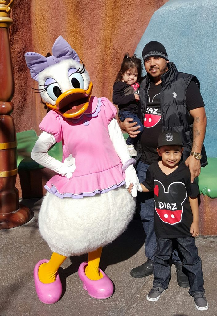 A father and two children posing with Daisy Duck